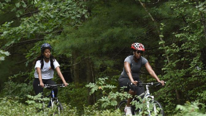 First lady Michelle Obama, right, and daughter Malia, bike in West Tisbury, Mass., on Martha's Vineyard, Saturday, Aug. 22, 2015. Obama and his family vacation every August on Martha's Vineyard. (AP Photo/Susan Walsh)