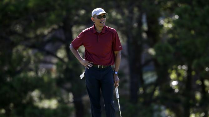 President Barack Obama stands on a green while golfing Friday, Aug. 14, 2015, at Farm Neck Golf Club, in Oak Bluffs, Mass., on the island of Martha's Vineyard. The president, first lady Michelle Obama, and daughter Sasha are vacationing on the island. (AP Photo/Steven Senne)