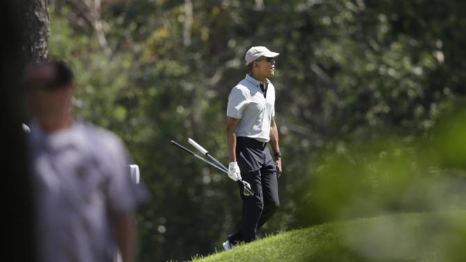 President Barack Obama carries clubs as he walks toward a green while golfing Wednesday, Aug. 12, 2015, at Farm Neck Golf Club, in Oak Bluffs, Mass., on the island of Martha's Vineyard. The president, first lady Michelle Obama, and daughter Sasha are vacationing on the island. A law enforcement official watches at left. (AP Photo/Steven Senne)