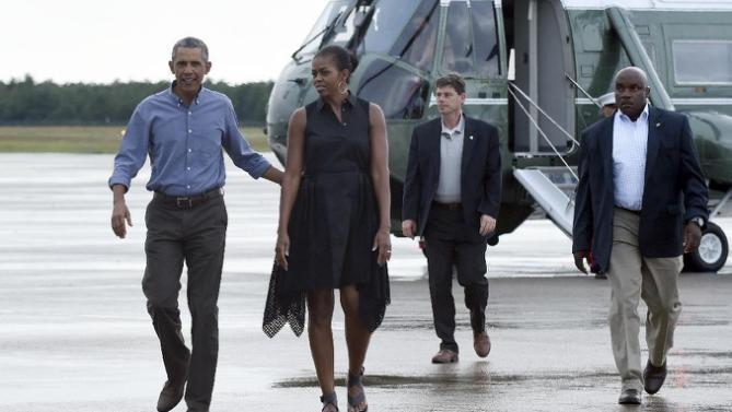 President Barack Obama and first lady Michelle Obama walk over to greet people before boarding Air Force One at Air Station Cape Cod, in Mass., Sunday, Aug. 23, 2015. The president is returning to Washington after he and his family spent more than two weeks vacationing on the Massachusetts island of Martha's Vineyard. (AP Photo/Susan Walsh)