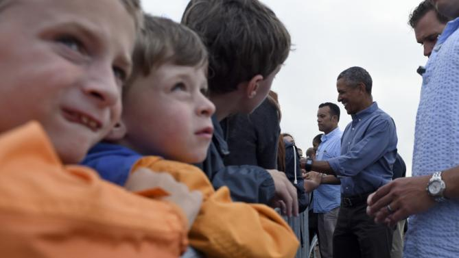 President Barack Obama greets people before boarding Air Force One at Air Station Cape Cod, in Mass., Sunday, Aug. 23, 2015. The president is returning to Washington after he and his family spent more than two weeks vacationing on the Massachusetts island of Martha's Vineyard. (AP Photo/Susan Walsh)