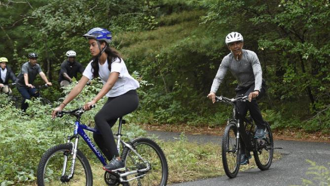 President Barack Obama, right, rides a bike with his daughter Malia, left, in West Tisbury, Mass., on Martha's Vineyard, Saturday, Aug. 22, 2015. Obama and his family vacation every August on Martha's Vineyard. (AP Photo/Susan Walsh)