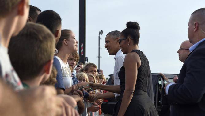 President Barack Obama and first lady Michelle Obama greet people after arriving at Vineyard Haven on Martha's Vineyard, Mass., Friday, Aug. 7, 2015. The president is returning to his summer vacation spot of choice, the Massachusetts island of Martha's Vineyard, for more than two weeks of hoped-for rest coupled with extended pursuit of his favorite leisure sport: golf. (AP Photo/Susan Walsh)
