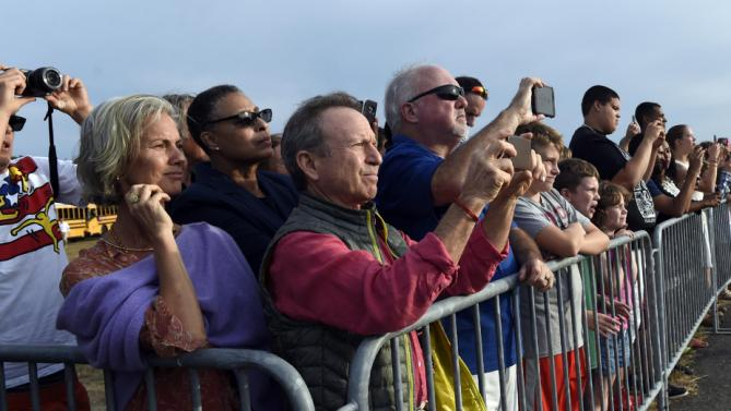 People watch as Marine One with President Barack Obama, first lady Michelle Obama, and daughter Sasha Obama, on board arrives at Vineyard Haven on Martha's Vineyard, Mass., Friday, Aug. 7, 2015. The president is returning to his summer vacation spot of choice, the Massachusetts island of Martha's Vineyard, for more than two weeks of hoped-for rest coupled with extended pursuit of his favorite leisure sport: golf. (AP Photo/Susan Walsh)
