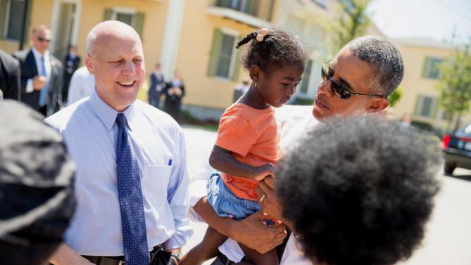 President Barack Obama, accompanied by New Orleans Mayor Mitch Landrieu, left, holds a young girl as he greets residents in the the Tremé neighborhood in New Orleans, Thursday, Aug. 27, 2015, for the 10th anniversary since the devastation of Hurricane Katrina. Tremé is one of the oldest black neighborhoods in America, which borders the French Quarter just north of Downtown. (AP Photo/Andrew Harnik)