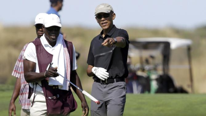 President Barack Obama, center, receives a club from a caddy, front left, while golfing at Vineyard Golf Club, in Edgartown, Mass., on the island of Martha's Vineyard, Monday, Aug. 10, 2015. The president is staying on Martha's Vineyard with first lady Michelle Obama and daughter Sasha for a 17-day island retreat. (AP Photo/Steven Senne)