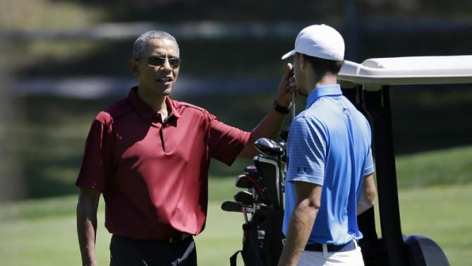President Barack Obama speaks with NBA basketball player Stephen Curry while golfing, Friday, Aug. 14, 2015, at Farm Neck Golf Club, in Oak Bluffs, Mass., on the island of Martha's Vineyard. The president, first lady Michelle Obama, and daughter Sasha are vacationing on the island. (AP Photo/Steven Senne)
