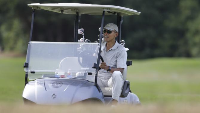 President Barack Obama drives a golf cart while golfing Saturday, Aug. 8, 2015, at Farm Neck Golf Club, in Oak Bluffs, Mass., on the island of Martha's Vineyard. Obama is spending his first full day of vacation on the island playing golf. (AP Photo/Steven Senne)