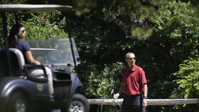 President Barack Obama, right, looks down the fairway while golfing Friday, Aug. 14, 2015 , at Farm Neck Golf Club, in Oak Bluffs, Mass., on the island of Martha's Vineyard. The president, first lady Michelle Obama, and daughter Sasha are vacationing on the island. (AP Photo/Steven Senne)