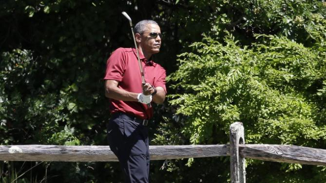 President Barack Obama follows through on a swing while golfing, Friday, Aug. 14, 2015, at Farm Neck Golf Club, in Oak Bluffs, Mass., on the island of Martha's Vineyard. The president, first lady Michelle Obama, and daughter Sasha are vacationing on the island. (AP Photo/Steven Senne)