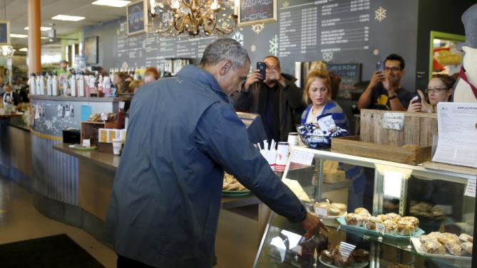 U.S. President Barack Obama makes a pastry order at Snow City Cafe in Anchorage, Alaska, September 1, 2015. Obama on Tuesday proposed a faster timetable for buying a new heavy icebreaker for the U.S. Arctic, where quickly melting sea ice has spurred more maritime traffic, and the United States has fallen far behind Russian resources. The move, part of a push to convince Americans to support Obama's plans to curb climate change, has long been urged by Arctic advocates as climate change opens up the region to more shipping, mining and drilling. REUTERS/Jonathan Ernst