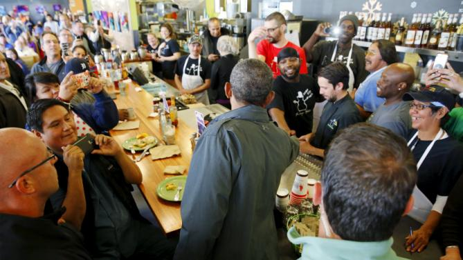 U.S. President Barack Obama greets people at Snow City Cafe in Anchorage, Alaska, September 1, 2015. Obama on Tuesday proposed a faster timetable for buying a new heavy icebreaker for the U.S. Arctic, where quickly melting sea ice has spurred more maritime traffic, and the United States has fallen far behind Russian resources. The move, part of a push to convince Americans to support Obama's plans to curb climate change, has long been urged by Arctic advocates as climate change opens up the region to more shipping, mining and drilling. REUTERS/Jonathan Ernst