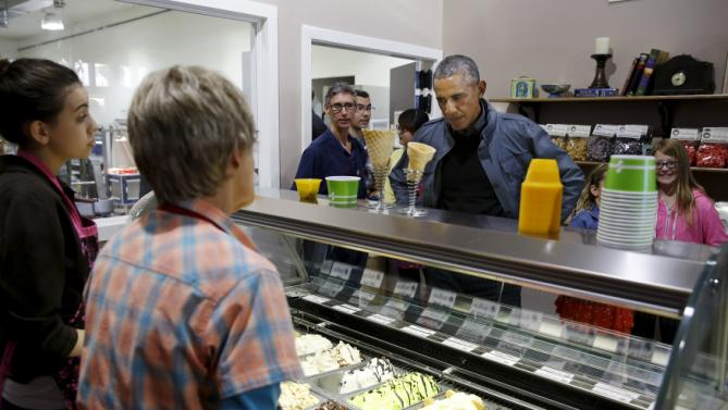 U.S. President Barack Obama makes a selection at the Sweet Darlings ice cream shop before taking a boat tour of Kenai Fjords National Park in Seward, Alaska September 1, 2015. During a three-day visit Obama is also slated to meet people in remote Arctic communities whose way of life is affected by rising ocean levels, creating images designed to build support for regulations to curb carbon emissions. REUTERS/Jonathan Ernst
