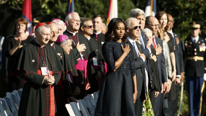 U.S. first lady Michelle Obama stands with U.S. bishops and members of the President Barack Obama's cabinet during an arrival ceremony for Pope Francis at the White House in Washington September 23, 2015. REUTERS/Kevin Lamarque