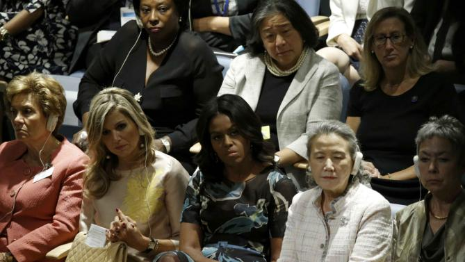 U.S. first lady Michelle Obama (C) listens while U.S. President Barack Obama addresses attendees during the 70th session of the United Nations General Assembly at the U.N. headquarters in New York September 28, 2015. REUTERS/Carlo Allegri