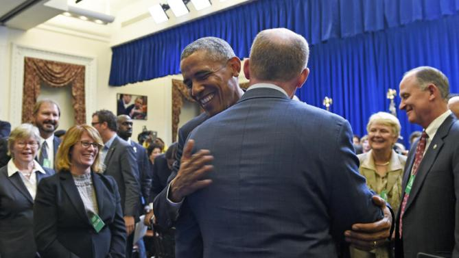 President Barack Obama hugs Illinois Senate President Pro Tempore Don Harmonas he meets with state legislators in the Eisenhower Executive Office Building in part of the White House complex in Washington, Wednesday, Sept. 30, 2015. (AP Photo/Susan Walsh)