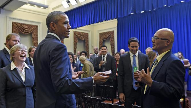 President Barack Obama holds a coin given to him by Hawaii State Senator Will Espero, right, as he meets with state legislators in the Eisenhower Executive Office Building in part of the White House complex in Washington, Wednesday, Sept. 30, 2015. (AP Photo/Susan Walsh)