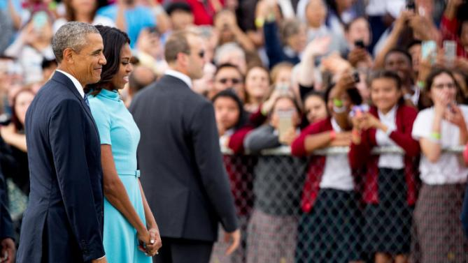 President Barack Obama and first lady Michelle Obama watch as Pope Francis motorcade departs Andrews Air Force Base, Md., Tuesday, Sept. 22, 2015. (AP Photo/Andrew Harnik)