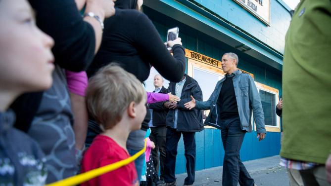 President Barack Obama greets people in downtown Seward, Alaska, Tuesday, Sept. 1, 2015, after takes a hike to view the Exit Glacier. Obama is on a historic three-day trip to Alaska aimed at showing solidarity with a state often overlooked by Washington, while using its glorious but changing landscape as an urgent call to action on climate change. (AP Photo/Andrew Harnik)