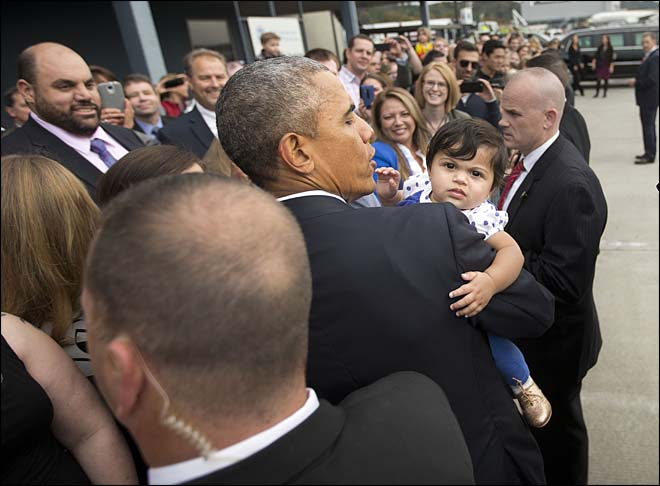 President Barack Obama carries a child as he greets people on the tarmac upon his arrival at King County International Airport in Seattle, Friday, Oct. 9, 2015. Obama is scheduled to attend a democratic fundraiser event with Sen. Patty Murray, D-Wash. He's is also attending fundraisers in San Francisco and Los Angeles as part of a four-day West Coast tour. (AP Photo/Pablo Martinez Monsivais)
