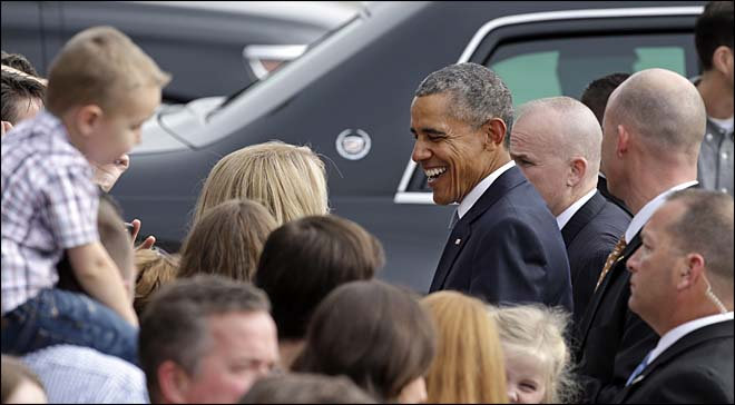 President Barack Obama greets a small group of people on his arrival Friday, Oct. 9, 2015, at King County Airport in Seattle. Obama was in town to attend a pair of fundraisers, following a stop Roseburg, Ore., where he visited families of victims of the shooting rampage there last week. (AP Photo/Elaine Thompson)