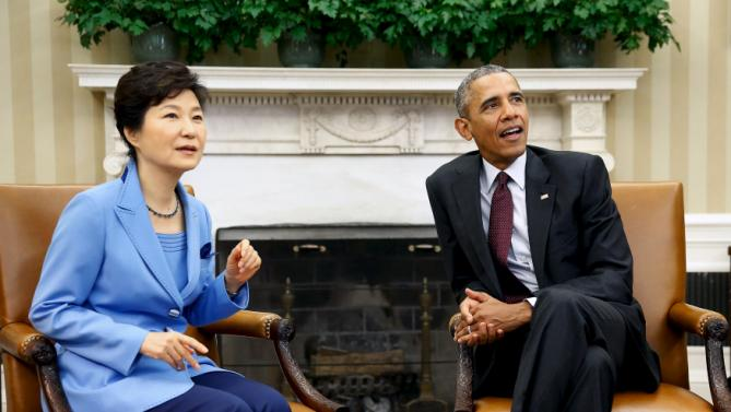 U.S. President Barack Obama (R) and South Korea's President Park Geun-hye react to jostling South Korean media as they sit down for their meeting in the Oval Office the White House in Washington, October 16, 2015. REUTERS/Jonathan Ernst