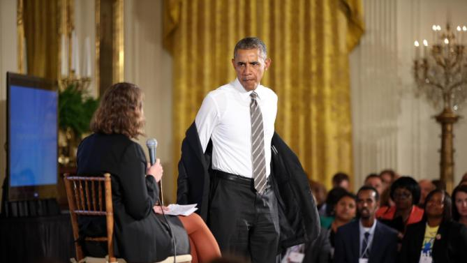 President Barack Obama takes off his jacket as he arrives to participate in a conversation co-hosted by coworker.org during the White House Summit on Worker Voice in the East Room of the White House in Washington, Wednesday, Oct. 7, 2015, with workers, employers, unions, organizers and other advocates and experts on how to energize a new generation of Americans to come together and recognize the potential power of their voice at work. On stage is Michelle Miller, co-founder of coworker.org. (AP Photo/Andrew Harnik)