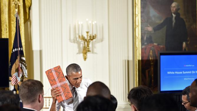 President Barack Obama shakes a present that her received following a conversation co-hosted by coworker.org at the White House Summit on Worker Voice in the East Room of the White House in Washington, Wednesday, Oct. 7, 2015. Participants included workers, employers, unions, organizers and other advocates and experts on how to energize a new generation of Americans to come together and recognize the potential power of their voice at work. (AP Photo/Susan Walsh)