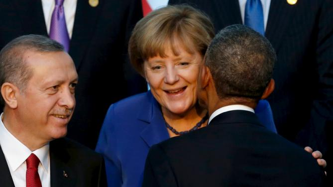 U.S. President Barack Obama (R, back to camera) greets Germany's Chancellor Angela Merkel (C) with a kiss on the cheek as they gather for a family photo with fellow world leaders at the start of the G20 summit at the Regnum Carya Resort in Antalya, Turkey, November 15, 2015. Also pictured is Turkey's President Tayyip Erdogan. REUTERS/Jonathan Ernst