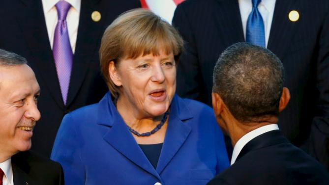 U.S. President Barack Obama (R, back to camera) greets Germany's Chancellor Angela Merkel (C) as they gather for a family photo with fellow world leaders at the start of the G20 summit at the Regnum Carya Resort in Antalya, Turkey, November 15, 2015. Also pictured is Turkey's President Tayyip Erdogan. REUTERS/Jonathan Ernst