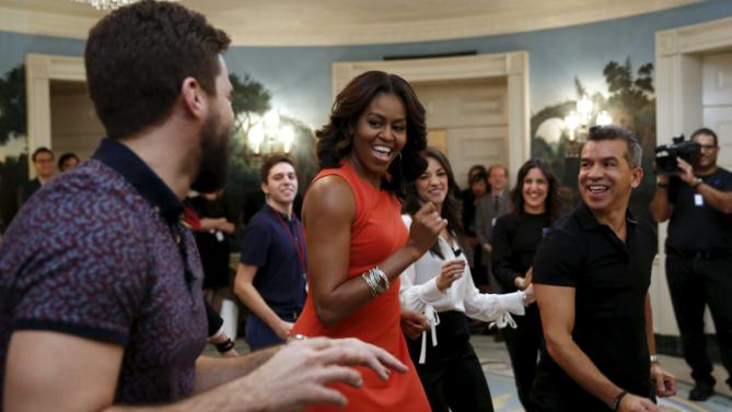 U.S. first lady Michelle Obama dances with actor Josh Segarra (L) and choreographer Sergio Trujillo (R) during a student workshop honoring the history of Broadway at the White House in Washington November 16, 2015. In the background in white is actress Ana Villafane. REUTERS/Kevin Lamarque