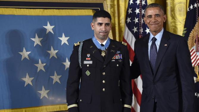 President Barack Obama stands with Medal of Honor recipient retired U.S. Army Capt. Florent Groberg during a ceremony in the East Room of the White House in Washington, Thursday, Nov. 12, 2015, honoring Groberg for his actions during combat operations in Afghanistan. (AP Photo/Susan Walsh)