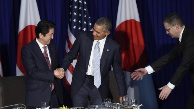 U.S. President Barack Obama, center, gets caught in his chair as he stands to shake hands with Japan's Prime Minister Shinzo Abe, left, during a bilateral meeting at the Asia-Pacific Economic Cooperation summit in Manila, Philippines, Thursday, Nov. 19, 2015. (AP Photo/Susan Walsh)