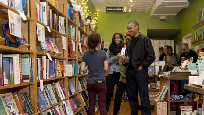 President Barack Obama, right, joined by his daughters Malia and Sasha, talks with manager Anna Thorn, left, shops at Upshur Street Books on Small Business Saturday in Washington, Saturday, Nov. 28, 2015. (AP Photo/Carolyn Kaster)