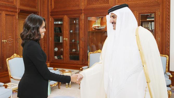 In this photo made available by the Qatar News Agency, QNA, U.S. First Lady Michelle Obama shakes hands with Qatar Emir Sheik Tamim bin Hamad Al-Thani in Doha, Qatar, Tuesday, Nov. 3, 2015. (Qatar Government/QNA via AP)