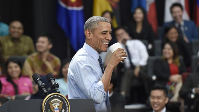 President Barack Obama smiles while holding a cup during the Young Southeast Asian Leaders Initiative (YSEALI) town hall at Taylor's University in Kuala Lumpur, Malaysia, Friday, Nov. 20, 2015. (AP Photo/Susan Walsh)