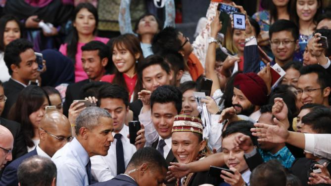 "U.S. President Barack Obama shakes hands with audience members as he finishes the Young Southeast Asian Leaders Initiative (YSEALI) town hall meeting at Taylor's University in Kuala Lumpur, Malaysia, Friday, Nov. 20, 2015. Obama urged young people in predominantly Muslim Malaysia on Friday to reject the ""terrible vision"" that drove the Paris attacks, offering an alternative vision in which traditional cultures coexist with a diverse modern world. (AP Photo/Vincent Thian)"