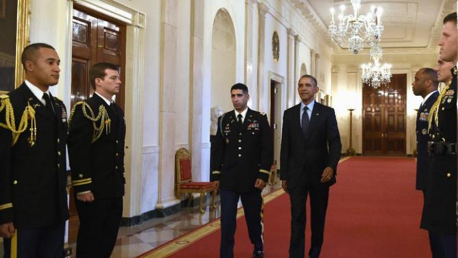 President Barack Obama and Medal of Honor recipient retired U.S. Army Capt. Florent Groberg, walk to the East Room of the White House in Washington, Thursday, Nov. 12, 2015, for ceremony honoring Groberg for his actions during combat operations in Afghanistan. (AP Photo/Susan Walsh)