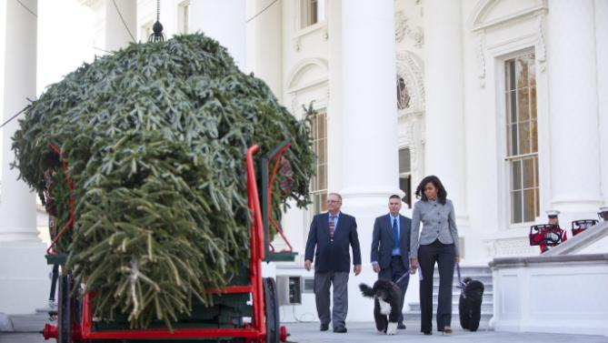 First lady Michelle Obama walks out with her dogs Bo and Sunny, to welcome the Official White House Christmas Tree to the White House in Washington, Friday, Nov. 27, 2015. This year's White House Christmas tree, which will be on display in the Blue Room, was presented by Jay Bustard, left, and his brother Glenn Bustard, center, from Bustard's Christmas Trees in Lansdale, PA. (AP Photo/Pablo Martinez Monsivais)