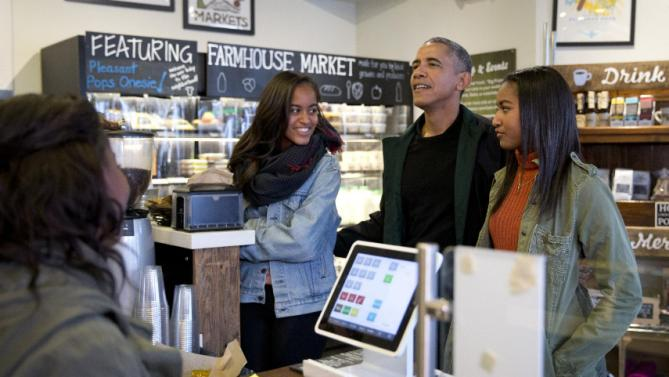 President Barack Obama, joined by his daughters Malia, left, and Sasha, right, orders at Pleasant Pops on Small Business Saturday in Washington, Saturday, Nov. 28, 2015. (AP Photo/Carolyn Kaster)
