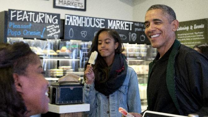 President Barack Obama, joined by his daughters Malia, left, and Sasha, in the background at right, orders a treat at Pleasant Pops on Small Business Saturday in Washington, Saturday, Nov. 28, 2015. (AP Photo/Carolyn Kaster)