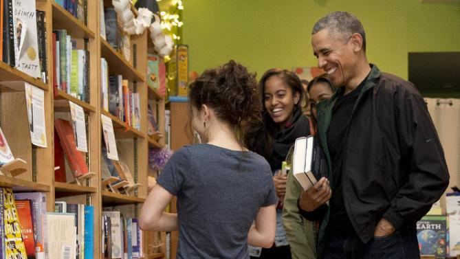 President Barack Obama, right, joined by his daughters Malia, second from left, and Sasha, second from right, talk with manager Anna Thorn, left, as they shop at Upshur Street Books on Small Business Saturday in Washington, Saturday, Nov. 28, 2015. (AP Photo/Carolyn Kaster)