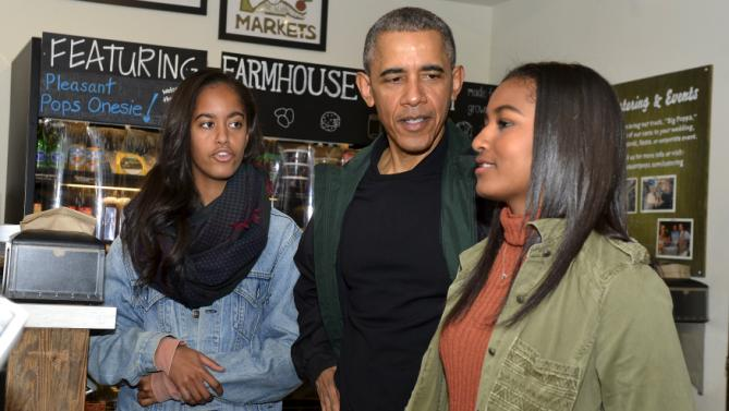 U.S. President Barack Obama (C) discusses with his daughters Sasha (R) and Malia before purchasing items at Pleasant Pops in Washington, November 28, 2015. Today is Small Business Saturday, which was started to encourage shoppers to buy locally and from brick-and-mortar stores, and serves as a counterpoint to the traditionally busy shopping days of Black Friday and Cyber Monday after the Thanksgiving holiday. REUTERS/Mike Theiler
