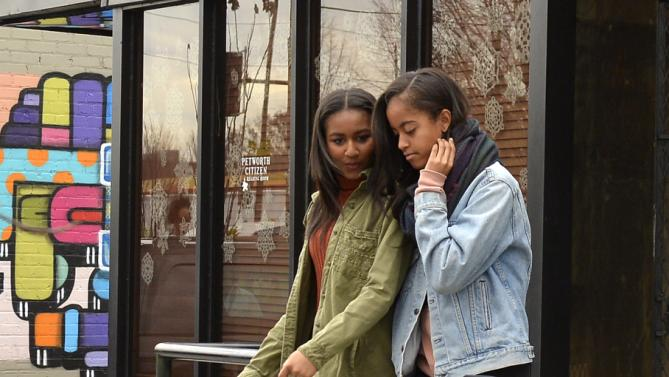 U.S. President Barack Obama's daughters Malia (R) and Sasha (L) depart the Upshur Street Books after visting the store to buy books with their father, in Washington, November 28, 2015. Today is Small Business Saturday, which was started to encourage shoppers to buy locally and from brick-and-mortar stores, and serves as a counterpoint to the traditionally busy shopping days of Black Friday and Cyber Monday after the Thanksgiving holiday. REUTERS/Mike Theiler