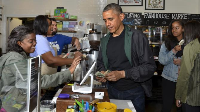 U.S. President Barack Obama (C) pays for purchases at Pleasant Pops, as daughters Malia and Sasha enjoy a popsicle, in Washington, November 28, 2015. Today is Small Business Saturday, which was started to encourage shoppers to buy locally and from brick-and-mortar stores, and serves as a counterpoint to the traditionally busy shopping days of Black Friday and Cyber Monday after the Thanksgiving holiday. REUTERS/Mike Theiler
