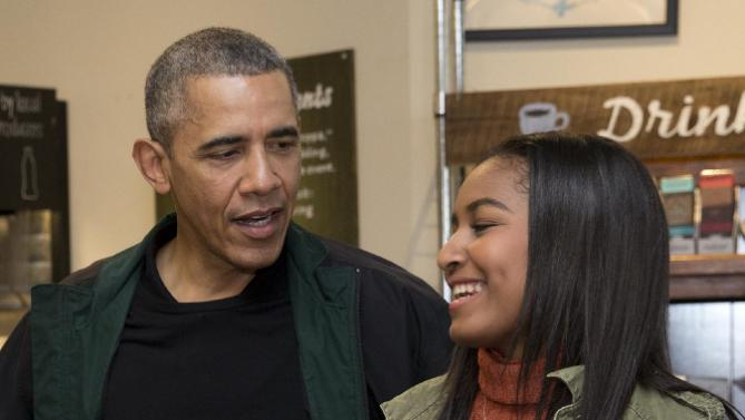 President Barack Obama looks to his daughter Sasha, as they order at Pleasant Pops on Small Business Saturday in Washington, Saturday, Nov. 28, 2015. (AP Photo/Carolyn Kaster)