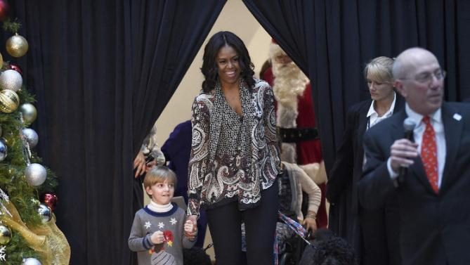 "First lady Michelle Obama walks with Stephen Orzechowski, 5, left, and Bo Obama, right, arrives to read ""Twas the Night Before Christmas"" to a group of children at the Children's National Health System in Washington, Monday, Dec. 14, 2015. Her appearance continued a first lady tradition that dates back more than 60 years to Bess Truman, who first brought holiday cheer to children not well enough to leave the hospital in time for Christmas. (AP Photo/Susan Walsh)"