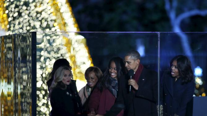 U.S. President Barack Obama with First Lady Michelle Obama (R) and their daughter Malia push a button to light the National Christmas Tree on the Ellipse near the White House in Washington December 3, 2015. REUTERS/Yuri Gripas