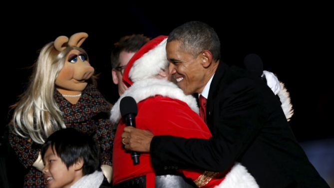 U.S. President Barack Obama hugs Santa Claus as Muppet Miss Piggy watches as Obama hosts the National Christmas Tree Lighting and Pageant of Peace ceremony on the Ellipse Washington December 3, 2015. REUTERS/Kevin Lamarque