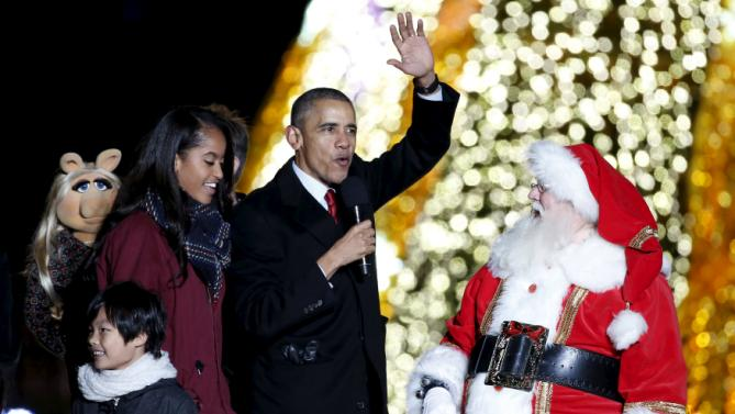 U.S. President Barack Obama waves next to a man dressed as Santa Claus during the National Christmas Tree Lighting and Pageant of Peace ceremony on the Ellipse near the White House in Washington December 3, 2015. REUTERS/Yuri Gripas